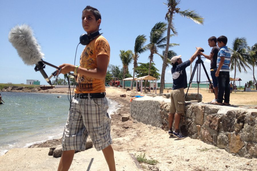 Photo of a young man holding a microphone as part of a film crew in Cuba