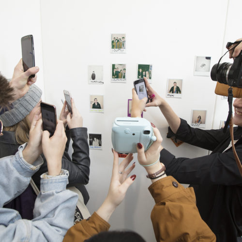 Young people hold phones and cameras to take photos