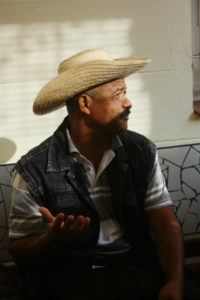 A Cuban man sits in dappled sunlight wearing a large straw hat