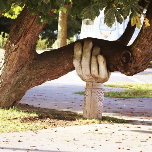 tree with wooden hand holding up a leaning branch