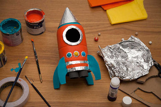 Image show a craft project space rocket coloured orange, blue and silve with a small tin of paint, card, glue and foil next to it